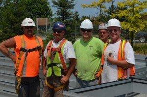 group of metal technicians standing near glass 4 plex